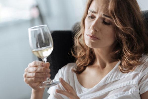 Женщина держит в руке бокал вина. Грустно на него смотрит