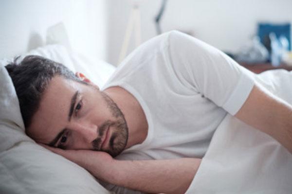 Расстроенный мужчина лежит в постели