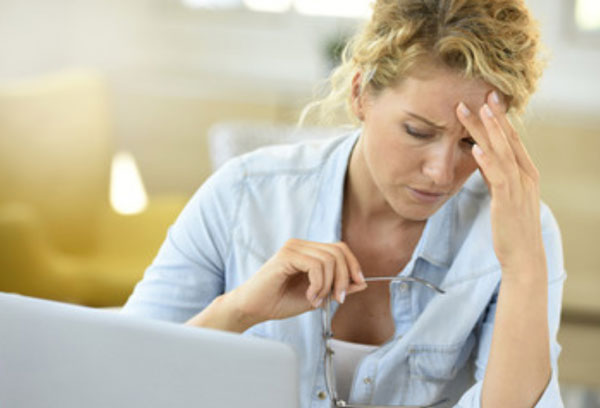 Уставшая женщина сидит перед ноутбуком