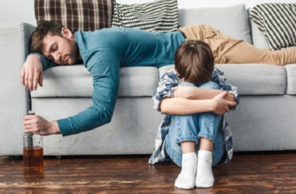 Мальчик сидит на полу. На диване лежит отец с бутылкой в руке