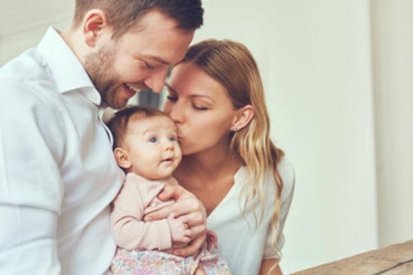 Папа и мама целуют малыша