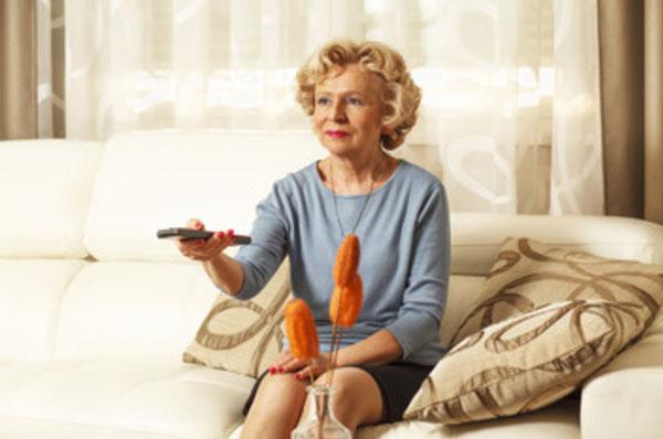 Бабушка сидит на диване и держит в руке пульт