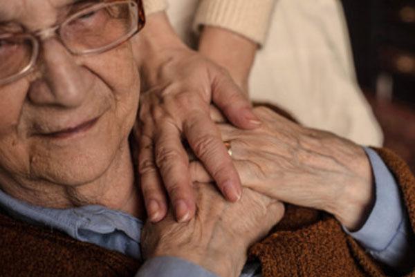 Дедушка сидит на кресле. Женщина держит его за руки