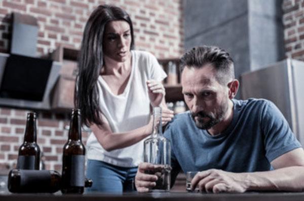 Мужчина с бутылкой сидит за столом. Рядом стоит женщина