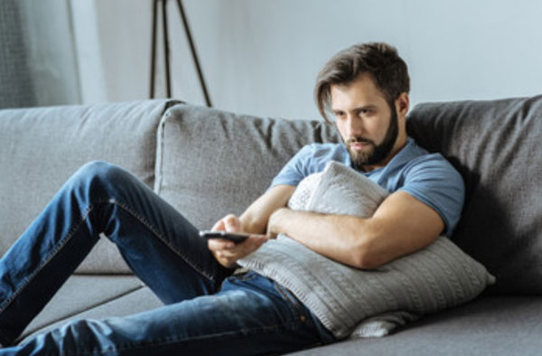 Мужчина в апатическом состоянии сидит перед телевизором