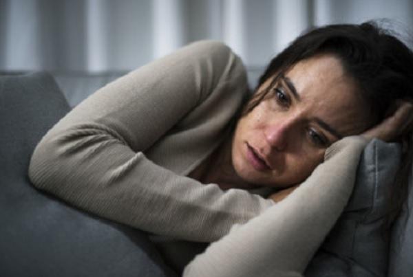 Замученная женщина лежит на диване