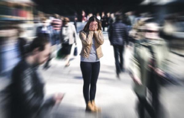 Женщина прячет лицо руками, вокруг нее много людей