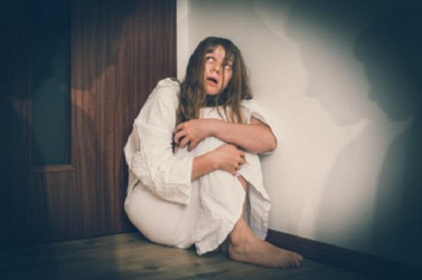 Испуганная женщина сидит на полу в углу
