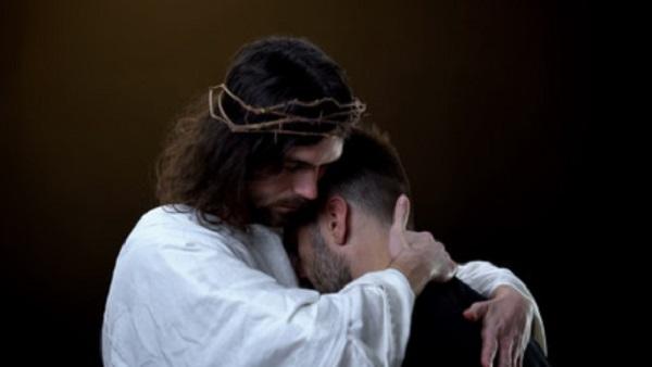Человек в образе Иисуса Христа прижимает к своему плечу мужчину