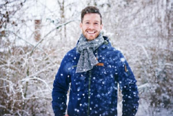 Счастливый мужчина стоит под снегом
