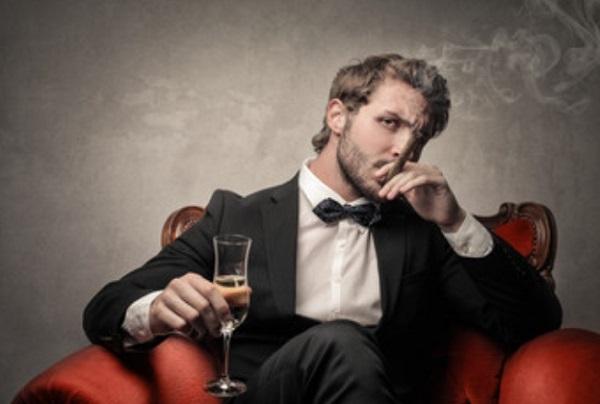 Мужчина с бокалом и сигарой в руках сидит в кресле