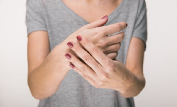 Женщина одной рукой держит свою вторую руку
