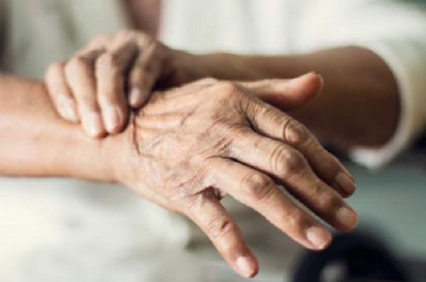 Пожилой человек пытается удержать свою руку, чтоб она перестала труситься