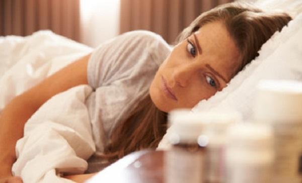Женщина в кровати смотрит на пузырьки с лекарствами