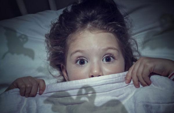 Девочка выглядывает из-под одеяла
