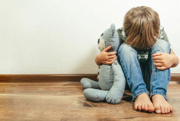 Ребенок сидит на полу, пряча свое лицо