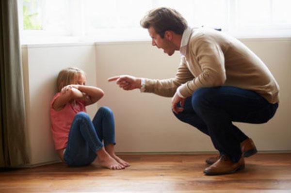 Отец ругает малыша, который сидит на полу