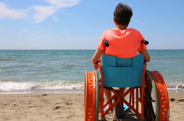 Мужчина на инвалидной коляске на берегу моря