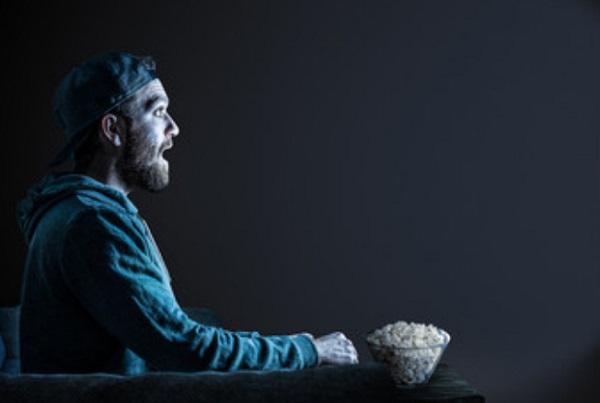 Мужчина сидит в темном зале