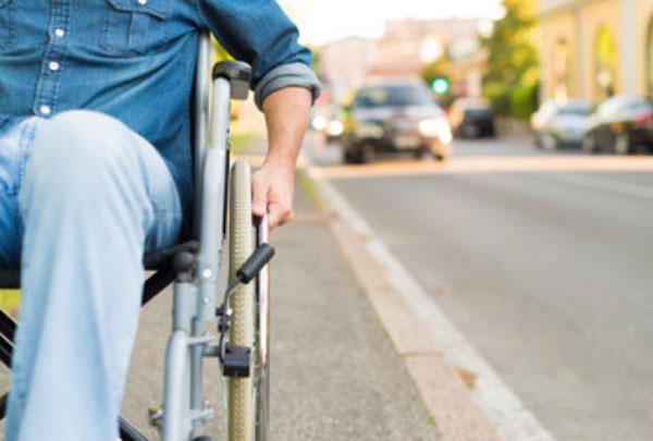 Мужчина едет по дороге на инвалидной коляске