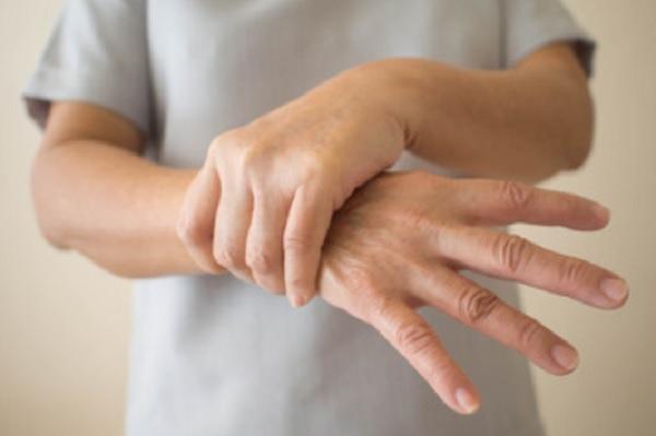 Человек удерживает руку, чтоб предупредить дрожь