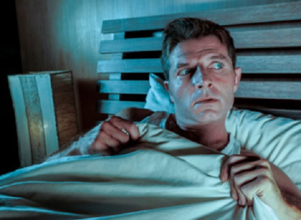 Мужчина в кровати испытывает тревогу
