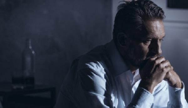 Мужчина в депрессии. На заднем плане бутылка