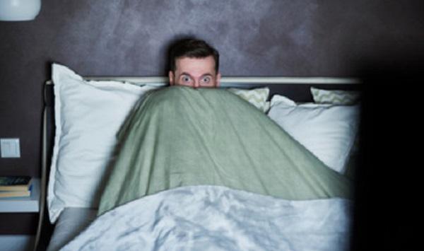 Очень испуганный мужчина боится выглядывать из-под одеяла