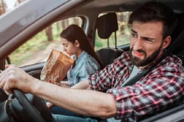 Девушка на пассажирском сидении держит бумажный пакет в руках