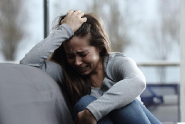 Женщина плачет, сидя на диване