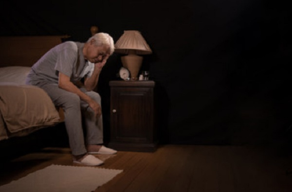 Замученный мужчина сидит на кровати