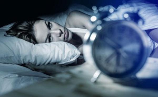 Женщина лежит с открытыми глазами, смотрит на часы