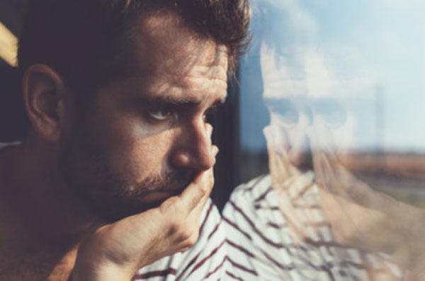 Мужчина грустит у окна