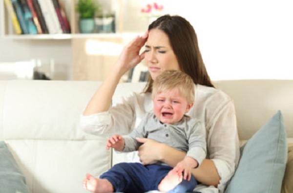 Женщина держит на руках ребенка, который плачет. Женщина хватается за голову
