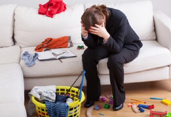 Женщина в костюме сидит на диване. Рядом разброшенные игрушки и одежда