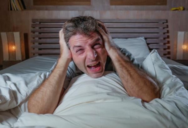 Мужчина в кровати. Кричит и хватается за голову