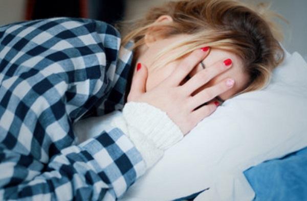 Женщина в постели прячет лицо рукой