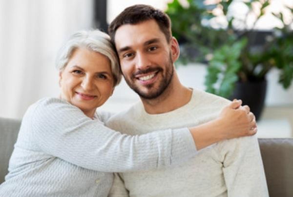 Пожилая мама помогает взрослому сыну