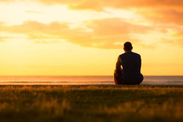 Мужчина сидит на земле, встречает закат