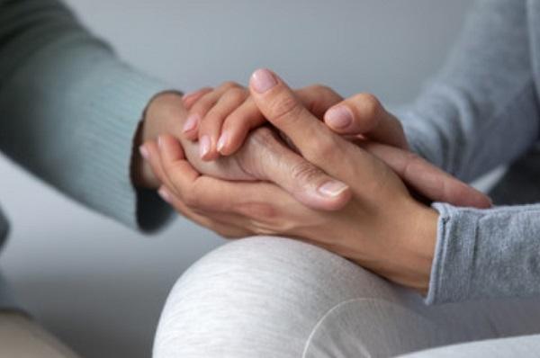 Рука родителя обнимает руку ребенка