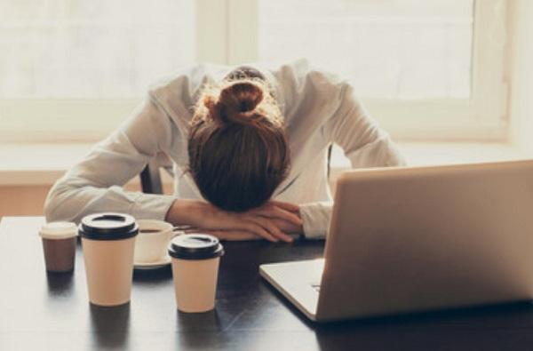 Женщина опустила голову. Рядом с ней стаканы с кофе и открытый ноутбук