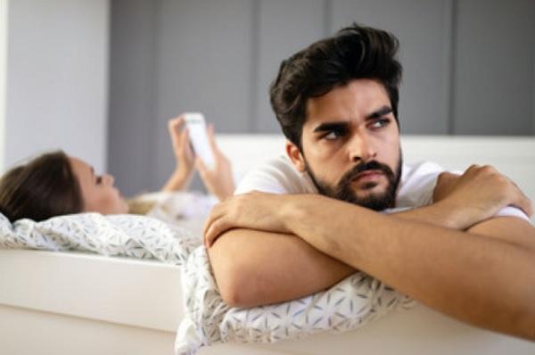Девушка смотрит в смартфон. Парень не доволен