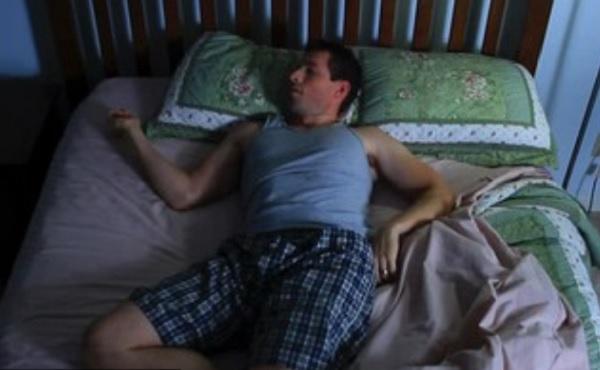 Мужчина лежит в кровати в неудобной позе