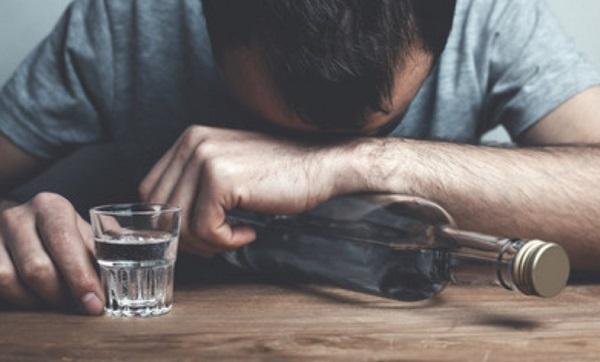 Мужчина с бутылкой в руке склонил голову на стол