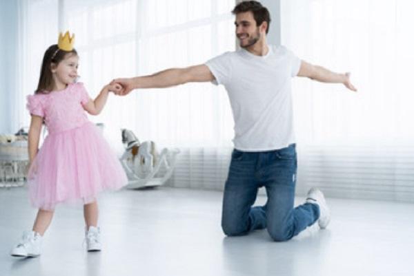 Девочка с короной на голове танцует с папой