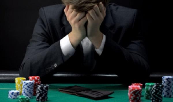 Мужчина сидит за игровым столом с пустым кошельком