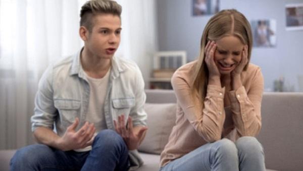 Парень что-то говорит девушке. Она плачет