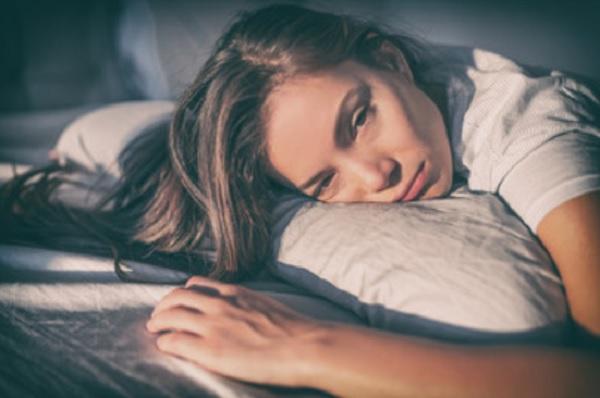 Уставшая женщина лежит на подушке