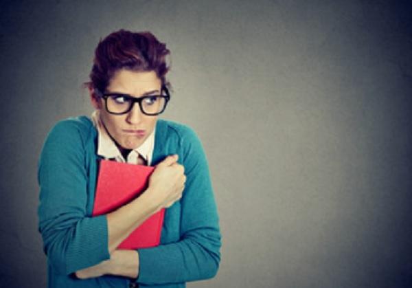 Женщина в очках прижимает к себе папку, испуганно смотрит