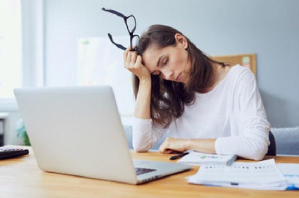 уставшая женщина сидит за ноутбуком